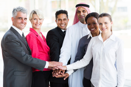 afro arab: group of successful business team putting their hands together