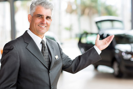 handsome senior vehicle salesman presenting new cars at showroom photo