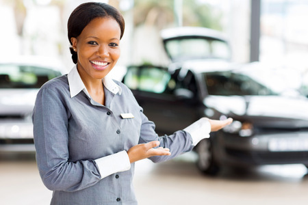 friendly african car saleswoman presenting new vehicles photo