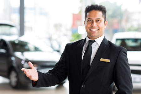 happy young indian car dealer standing inside showroom photo