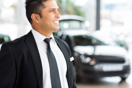 confident vehicle dealership salesman in showroom photo
