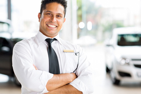 cheerful indian vehicle salesman with arms crossed photo