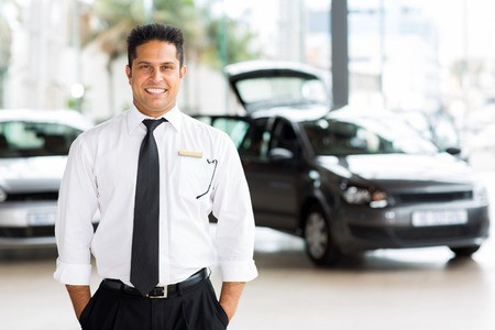 auto sales: handsome indian man working at vehicle showroom