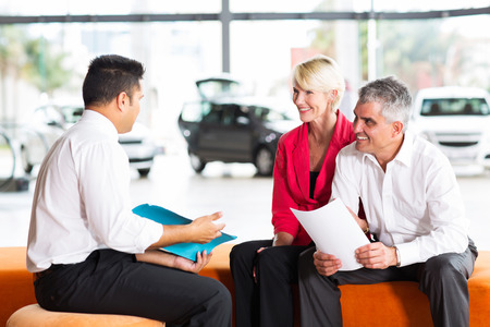 agent: vehicle salesman explaining contract to senior couple before buying a car Stock Photo