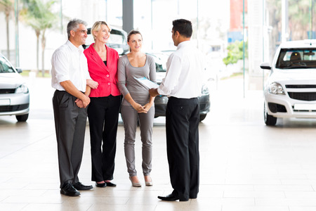 vehicle salesman explaining contract to family before purchasing a car Stock Photo