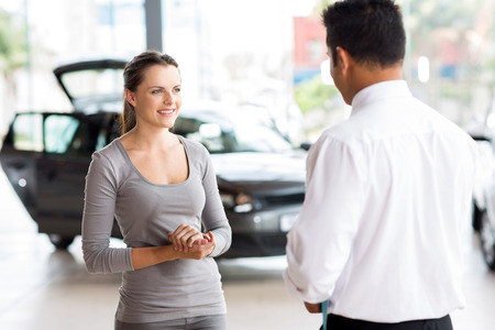 friendly car salesman talking to a young woman inside showroom photo