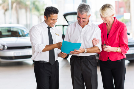 mature couple buying a new car at vehicle showroom photo