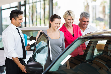 indian happy family: handsome car salesman showing a new car to a family