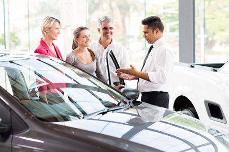 vehicle salesman showing new car to a family photo