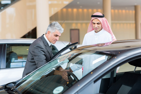 middle aged car dealer showing new car to potential Arabian buyer photo