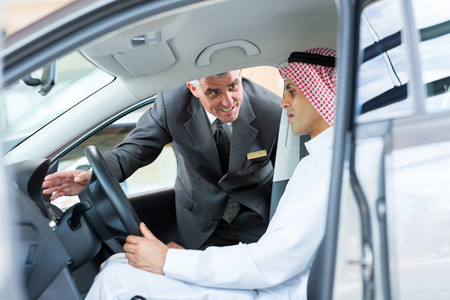 friendly senior salesman explaining car features to arabian man photo