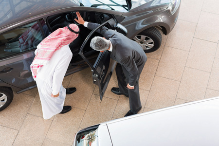 overhead view of vehicle salesman selling a car to arabian man photo
