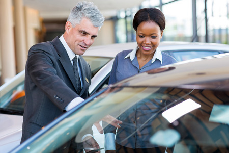 friendly mature car dealer showing new car to african customer photo