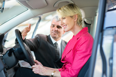 senior car sales consultant showing a new car to mature female customer photo