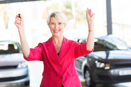 excited senior woman collecting her new car from dealership photo