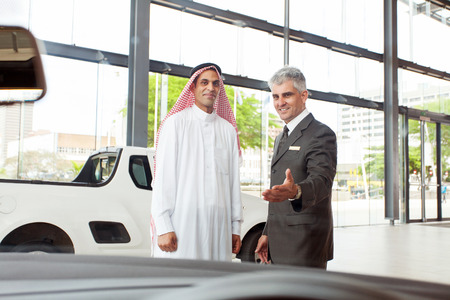 handsome senior car salesman selling a car to arabic man photo