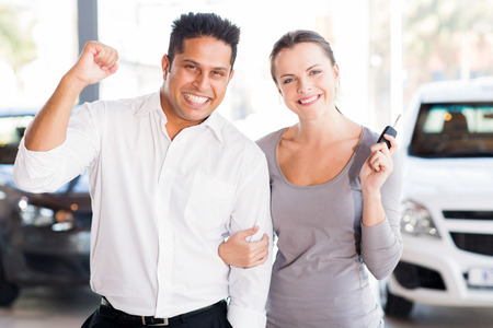 buying: excited young couple just bought a new car from dealership