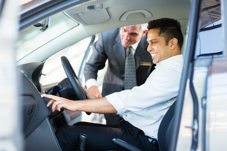 happy indian man checking car features at showroom photo