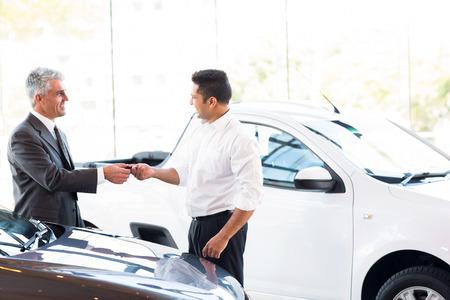 senior car salesman handing over new car key to customer at showroom photo