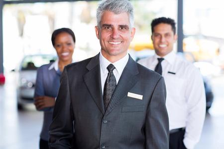 principal: portrait of senior car dealership principal with staff on background