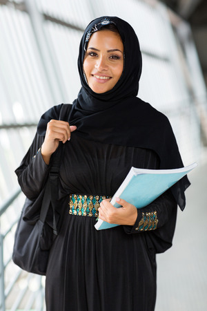 middle eastern clothes: happy female arabian college student holding a book