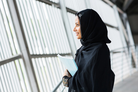 muslim girl: side view of pretty middle eastern college girl daydreaming