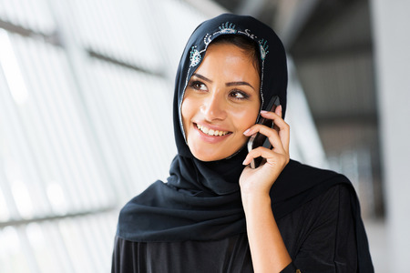 pretty middle eastern woman talking on mobile phone photo