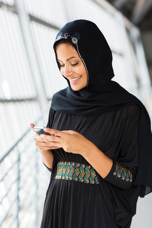 middle eastern clothes: happy islamic woman using smart phone Stock Photo