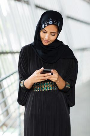 modern muslim woman reading email no smart phone photo