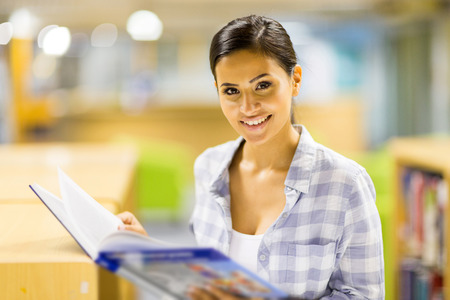 happy college girl reading a book in library photo