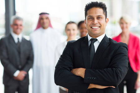 cheerful young indian businessman with team on background Stock Photo