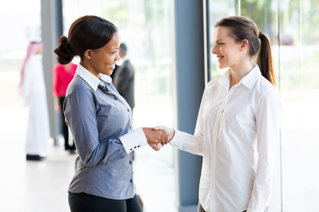 business woman standing: two beautiful businesswomen handshaking in office Stock Photo