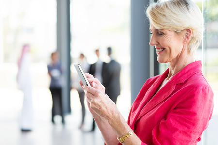email mooie middelbare leeftijd zakenvrouw lezing over smart phone