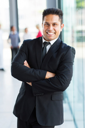 ethnic attire: happy indian business man standing in office Stock Photo