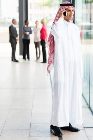 hombre arabe: hombre de negocios musulmán en la ropa tradicional hablando por teléfono celular