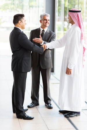senior translator introducing muslim businessman to business partner photo