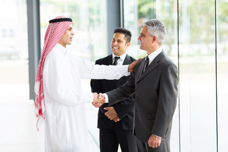 business handshake: multicultural business partners handshaking in office