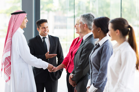 young translator introducing Arabian businessman to business partners photo