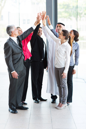 five people: happy business team giving high five in office Stock Photo