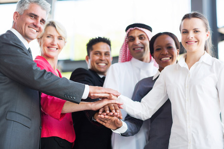 afro arab: close up of multiracial business team putting their hands together, focus on hands Stock Photo