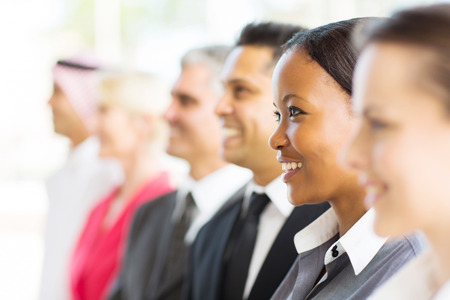 group of happy businesspeople looking away