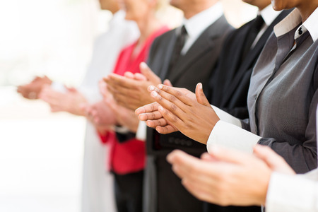 applauding: group of businesspeople clapping hands during meeting presentation