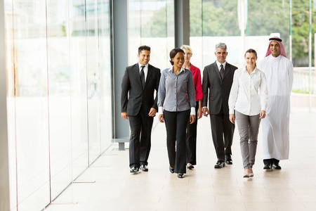 group of professional businesspeople walking in office building photo