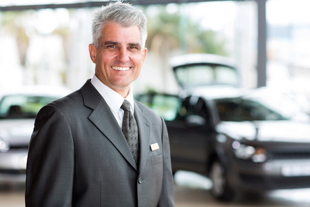 senior vehicle salesman working at a car dealer Stock Photo