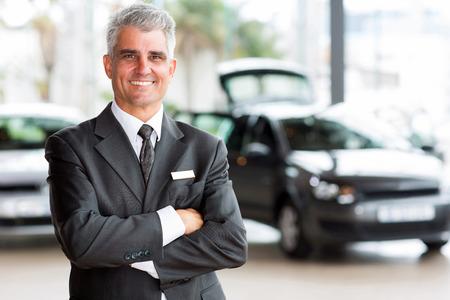 automobile sales: confident senior car dealer principal standing in showroom