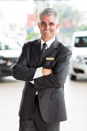 happy middle aged man working at car dealership photo