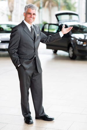 friendly car salesman doing welcoming gesture at car dealership photo