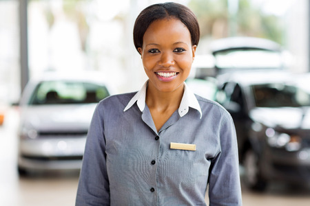 ethnic attire: portrait of african american saleswoman standing at car dealership