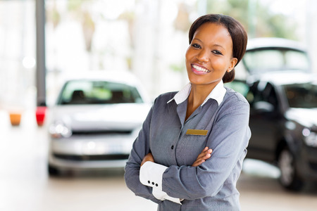 sales lady: pretty african vehicle saleswoman with arms crossed in showroom Stock Photo