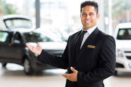 handsome indian salesman presenting new car to clients photo